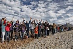 Folk i en fridsam demonstration på en strand som skyddar den från konstruktion Arkivfoton