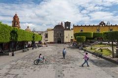 Folk i en fyrkant i den historiska mitten av staden av San Miguel de Allende, Mexico Arkivbilder