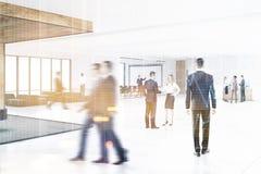 Folk i en kontorskorridor med en whiteboard som tonas Arkivfoton