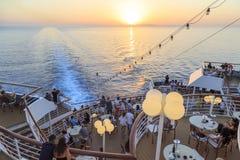 Folk i hållande ögonen på solnedgång för kryssningskepp över det aegean havet i grekiska öar, Grekland Royaltyfri Bild