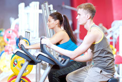 Folk i idrottshallen som gör cardio cykla utbildning Fotografering för Bildbyråer