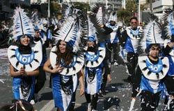 Folk i karnevaldr?kter som promenerar en gata arkivbild