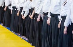 Folk i kimono- och hakamaanseende i en linje på kampsportutbildningsseminarium Arkivfoton