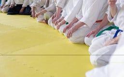 Folk i kimonosammanträde på tatami på kampsportutbildning Arkivfoto