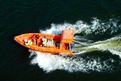 Folk i livräddareomslag i säkert fartyg för orange räddningsaktion royaltyfri foto