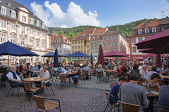 Folk i outdootkafé på central fyrkant i Heidelberg arkivfoto