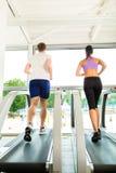 Folk i sportidrottshall på treadmillspring Royaltyfria Bilder