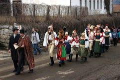 Folk i traditionella dräkter som firar vinterkarnevalet Arkivbilder