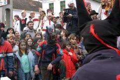 Folk i traditionella dräkter som firar vinterkarnevalet Arkivfoto