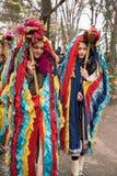 Folk i traditionella karnevaldräkter på den Kukeri festivalkukerlandiaen Yambol, Bulgarien Deltagare från Rumänien Royaltyfri Fotografi