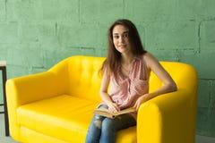 Folk-, inre- och utbildningsbegrepp - läsebok för ung kvinna på den gula soffan arkivbilder