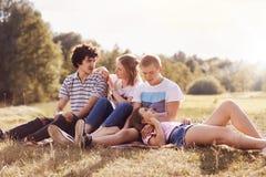 Folk, livsstil och vänbegrepp Glad två kläder för iklädd sommar för par tillfällig, spenderar fri tid i bygd, tycker om royaltyfri foto