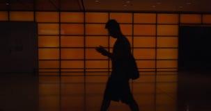 Folk med bagage i fattig tänd korridor av flygplatsterminalen stock video