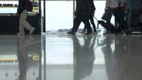 Folk med bagage som förbigår fönstret i flygplats