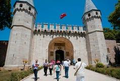 Folk med barn som går till och med porten av den historiska Topkapi slotten, Turkiet Royaltyfri Fotografi