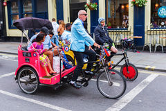 Folk med cirkuleringsrickshaws i London, UK Arkivfoto