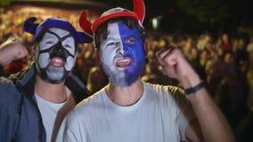 Folk med målarfärg på framsidahopp i fröjd som ska segras av socer eller fotbollsmatchen 4k stock video