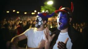 Folk med målarfärgen på framsidahopp i fröjd från segern av fotbollsmatchen arkivfilmer