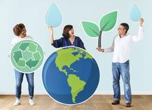 Folk med miljö- och återvinningsymboler Arkivbild