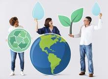 Folk med miljö- och återvinningsymboler Royaltyfria Bilder