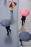 Folk med paraplyer Arkivfoto