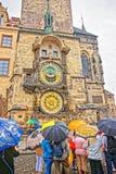 Folk med paraplyer på klockan av den gamla staden Hall Prague Arkivbild