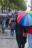 Folk med regnparaplyer i den regniga staden Royaltyfri Foto
