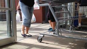 Folk med shoppingvagnen som går till och med dörrarna lager videofilmer