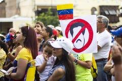 Folk med tecken på protesten mot Nicolas Maduro royaltyfri foto
