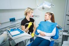 Folk-, medicin-, stomatology- och hälsovårdbegrepp - lycklig kvinnlig tandläkare som kontrollerar upp tålmodiga tonåriga flickatä arkivbild