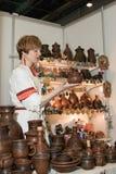 Folk mistress, showing pottery. Stock Photography