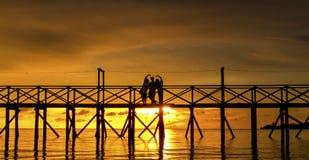 Folk mot en solnedgånghimmel Fotografering för Bildbyråer