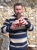 Folk musician playing a double flute Stock Photo