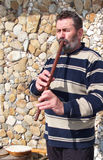 Folk musician playing a long flute Royalty Free Stock Photography