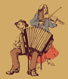 Folk musicians. Accordion player and gypsy woman with violin Stock Photography
