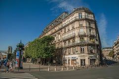 Folk och byggnader på hörngatan med blå himmel i Paris fotografering för bildbyråer