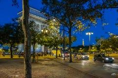 Folk och trafik som förbigår Arc de Triomphe i den Paris franc royaltyfria foton