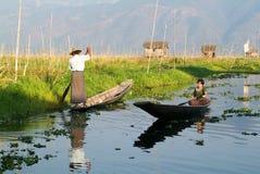 Folk på att ro ett fartyg på byn av Maing Thauk Arkivfoton
