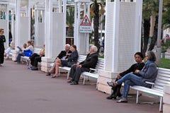 Folk på bänken på Promenade des Anglais, Nice, Frankrike Arkivbilder