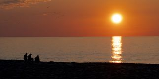 Folk på bakgrunden av solnedgången och havet på stranden royaltyfri bild