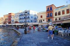 Folk på Chania strand med trottoargatakaféer, Kreta, G Royaltyfri Fotografi