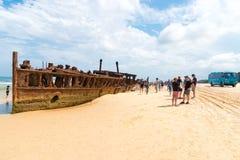Folk på den Maheno skeppsbrottet på 75 mil strand, en av de populäraste gränsmärkena på Fraser Island, Fraser Coast, Queensland,  Arkivbild