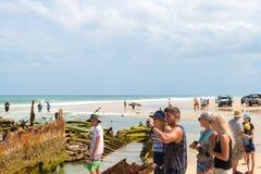 Folk på den Maheno skeppsbrottet på 75 mil strand, en av de populäraste gränsmärkena på Fraser Island, Fraser Coast, Queensland,  Arkivbilder
