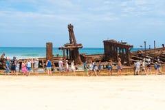 Folk på den Maheno skeppsbrottet på 75 mil strand, en av de populäraste gränsmärkena på Fraser Island, Fraser Coast, Queensland,  Arkivfoto