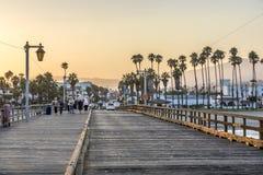 Folk på den sceniska gamla träpir i Santa Barbara i solnedgång Arkivfoto