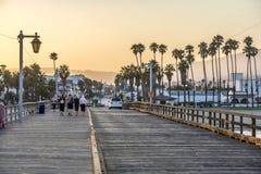Folk på den sceniska gamla träpir i Santa Barbara i solnedgång Royaltyfri Bild