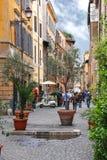 Folk på den smala pittoreska gatan i Rome, Italien Arkivfoto