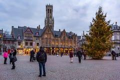Folk på den stora marknadsfyrkanten Markt i mitten av Bruges royaltyfria bilder