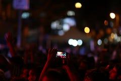 Folk på det friamusikfestivalen på natten Fotografering för Bildbyråer