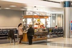 Folk på en återförsäljnings- kiosk i flygplats arkivfoto
